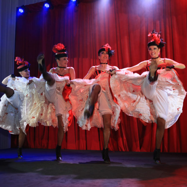 Two dancers dressed up in french cancans outfits on stage dancing