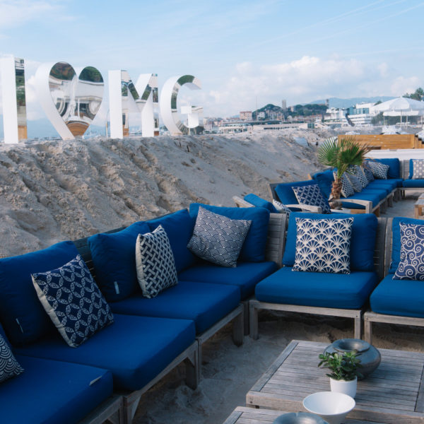Big silver letters for a branded beach and blue sofa on the beach for a networking lounge area during MAPIC