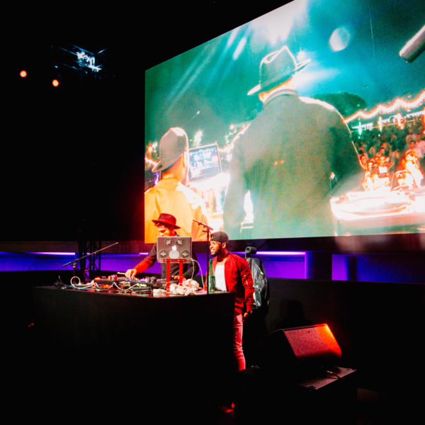 Giant led screen displaying images of te DJ from behin facing the audience