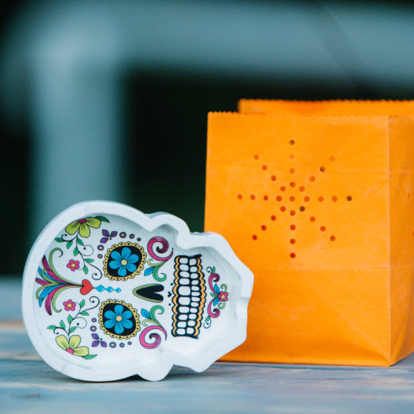 Candle in an orange bag with a calavera ashtray during a summer festival