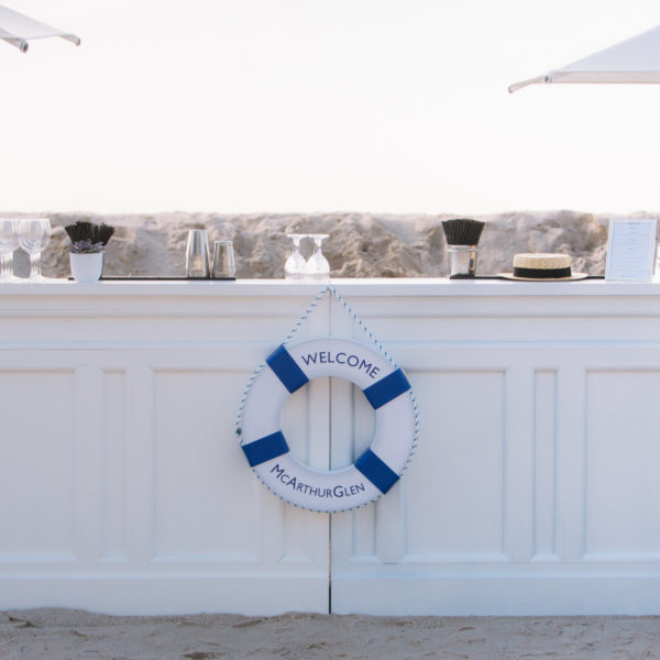 White bar with branded rubber ring in the front and white parasol with sand dune and sea in the background