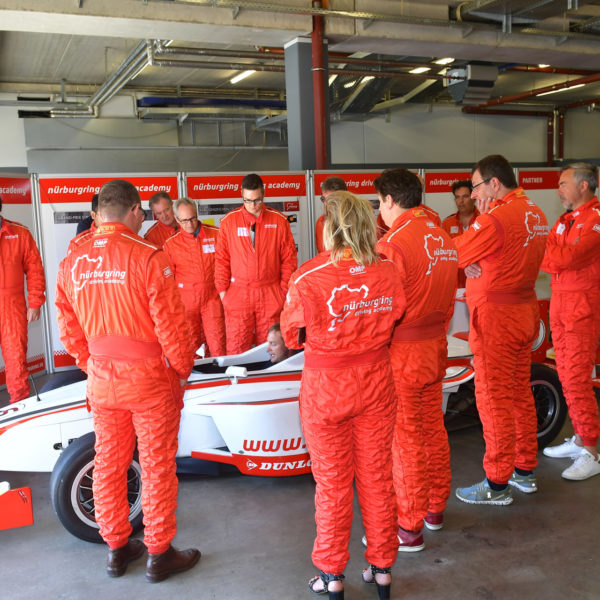 Guests around the racing car listening to the teachers