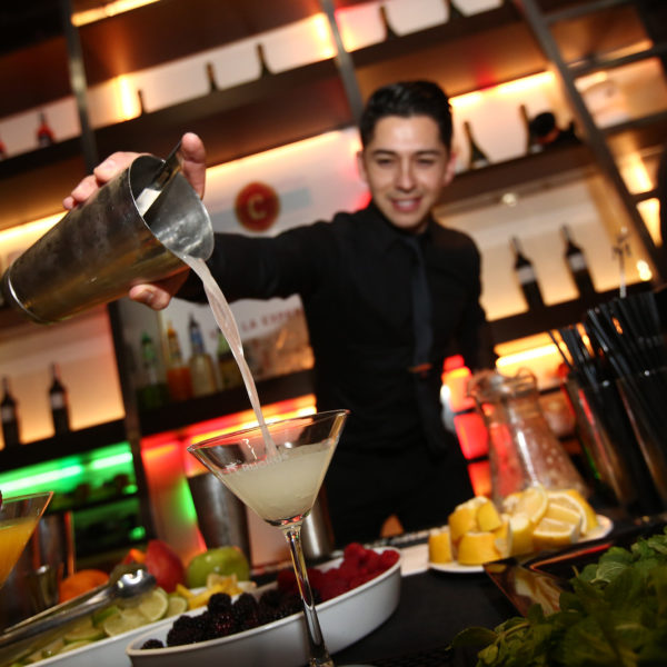 Bar tender preparing a cocktail during networking event in front of MWC