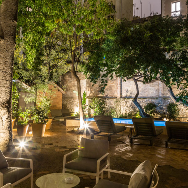 Hidden garden in a secret venue in Barcelona with a lighted swimming pool at night