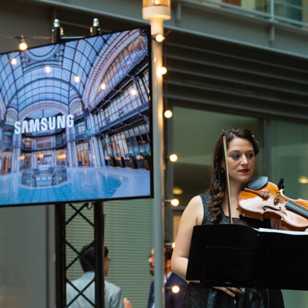"""Violinist playing on stage with TV screen on the side of the stage with the venue""""s image"""