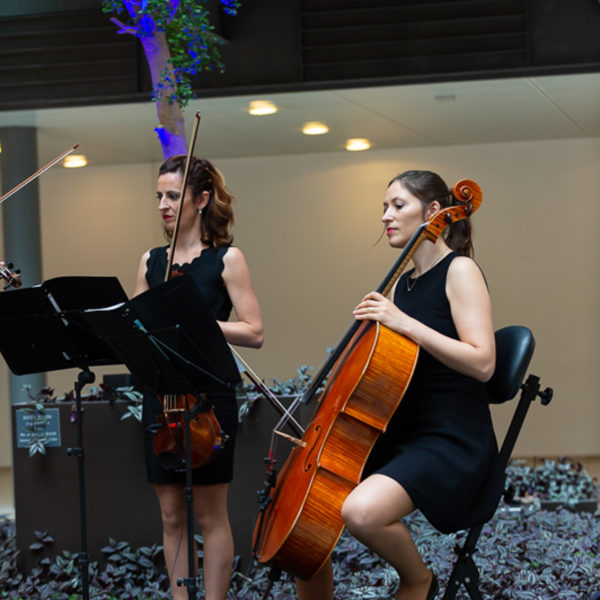 Cello and violinst playing on stage after the ribbon cutting ceremony