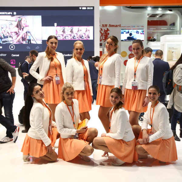 Hostesses at MWC booth during congress dressed with corporate colours